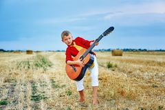 Romantic young boy with guitar in the field. Romantic boy with a guitar in the field . fashionable little musician in nature . children`s music education royalty free stock photos