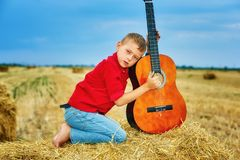 Romantic young boy with guitar in the field. Romantic boy with a guitar in the field . fashionable little musician in nature . children`s music education royalty free stock image