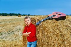 Romantic young boy with guitar in the field. Romantic boy with a guitar in the field . fashionable little musician in nature . children`s music education stock images