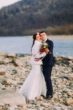 Romantic young bridal couple hugging on pebble riverside with forest hills as background Royalty Free Stock Image