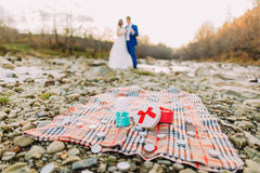 Romantic young bridal pair drinking wine on pebble river bank with hills and stream as background Royalty Free Stock Photography