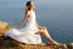 Romantic young bride in sitting on the cliff Stock Image