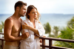 Romantic young couple balcony. Romantic young couple in sleepwear spending quality time on hotel balcony Royalty Free Stock Photography