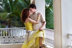 Romantic young couple on balcony in tropical rain. Romantic young couple on a balcony in a tropical rain Royalty Free Stock Image