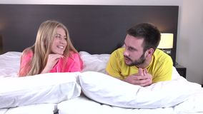 Romantic young couple in bed at home room. Romantic young couple in bed at home, beautiful blond girl with long hair and a snow-white smile, man stroking her stock video footage
