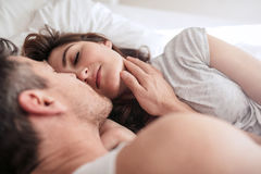 Romantic young couple on bed. Young women lying on bed with man. Romantic young couple on bed Royalty Free Stock Photography