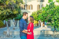Romantic young couple in bright red and blue clothes embracing on the mediterranean city street. Love, dating, romance. Lifestyle. And tourism concepts Stock Photo