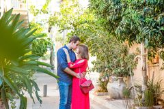 Romantic young couple in bright red and blue clothes embracing on the mediterranean old city street. Love, dating, romance. Lifest. Yle and tourism concepts Royalty Free Stock Photos