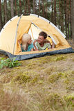 Romantic young couple camping in forest Stock Photo