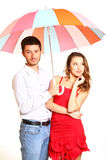 Romantic young couple with a colorful umbrella isolated on white Royalty Free Stock Photography
