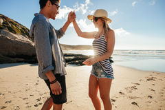 Romantic young couple dancing on the beach. Shot of young men and women dancing on the beach on a summer day. Romantic young couple dancing on the beach Stock Photos