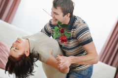 Romantic young couple dancing with rose. Romantic young couple dancing with red rose at home Royalty Free Stock Images