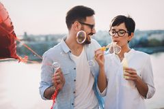 Romantic young couple dating outdoor and blowing bubbles. Romantic young couple in love dating outdoor and blowing bubbles Royalty Free Stock Images