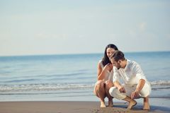 Romantic young couple draw heart shapes in the sand while on honeymoon. summer beach love concept. stock photography