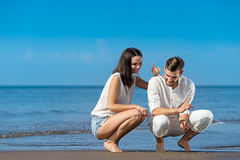 Romantic young couple draw shapes in the sand while on honeymoon. Summer beach love concept Stock Photography