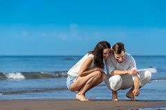Romantic young couple draw shapes in the sand while on honeymoon. Summer beach love concept Stock Photo