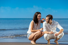 Romantic young couple draw shapes in the sand while on honeymoon. Royalty Free Stock Image