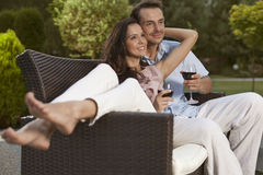 Romantic young couple on easy chair looking away in park Stock Images