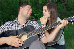 Romantic young couple embracing playing guitar Royalty Free Stock Images