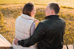 Romantic young couple enjoying autumn nature sitting in a close embrace, view from behind. Romantic young couple enjoying a date sitting in a close embrace on a Royalty Free Stock Images