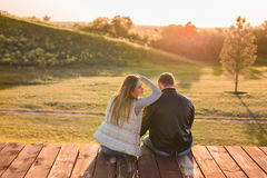 Romantic young couple enjoying autumn nature sitting in a close embrace, view from behind. Romantic young couple enjoying a date sitting in a close embrace on a Stock Image