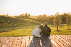 Romantic young couple enjoying autumn nature sitting in a close embrace, view from behind. Romantic young couple enjoying a date sitting in a close embrace on a Royalty Free Stock Photos