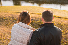 Romantic young couple enjoying autumn nature sitting in a close embrace, view from behind. Romantic young couple enjoying a date sitting in a close embrace on a Royalty Free Stock Photography