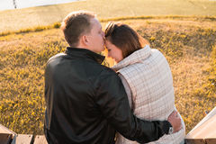 Romantic young couple enjoying autumn nature sitting in a close embrace, view from behind Stock Photography