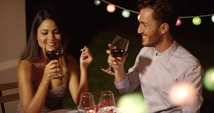Romantic young couple enjoying dinner and wine. At a restaurant smiling and chatting as they celebrate a special event stock video
