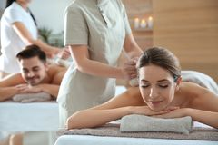 Romantic young couple enjoying herbal bag massage. In spa salon royalty free stock photos