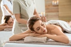 Romantic young couple enjoying herbal bag massage. In spa salon stock photography