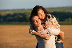 Romantic young couple having fun on wheaten field background at evening, summer season, girl riding on man back Stock Images