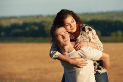 Romantic young couple having fun on wheaten field background at evening, summer season, girl riding on man back Royalty Free Stock Images