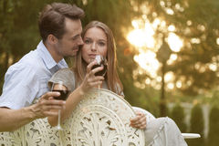 Romantic young couple having red wine on chairs in park Royalty Free Stock Photos