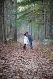 Romantic young couple holding hands and kissing in the woods stock image