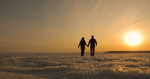 Romantic young couple holding hands and walking on the beach as the sun begins to set. stock video footage
