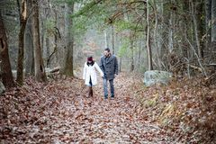 Romantic young couple holding hands walking in the woods. A romantic young couple holding hands and walking in the woods on a cold fall day with sun setting stock photos