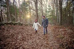 Romantic young couple holding hands walking in the woods. A romantic young couple holding hands and walking in the woods on a cold fall day with sun setting stock photography