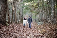 Romantic young couple holding hands walking in the woods. A romantic young couple holding hands and walking in the woods on a cold fall day with sun setting royalty free stock images