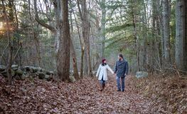Romantic young couple holding hands walking in the woods. A romantic young couple holding hands and walking in the woods on a cold fall day with sun setting royalty free stock photo