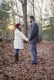 Romantic young couple holding hands in the woods. A romantic young couple holding hands face to face in the woods on a cold fall day with sun setting behind them stock image