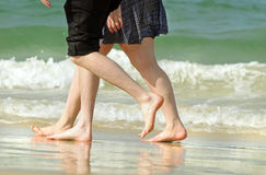 Romantic young couple on holiday walking along beach Stock Photos