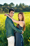 Romantic young couple in an intimate embrace. Romantic young couple in an intimate embrace turning to look at the camera as they standing in a colorful golden Royalty Free Stock Photography