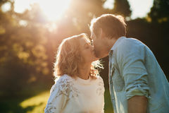 Romantic young couple kissing each other outside under the sun Royalty Free Stock Photos