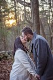 Romantic young couple kissing in the New England woods stock images