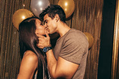 Romantic young couple kissing in the night club. Shot of romantic young couple kissing in the night club. Man and women in the pub Royalty Free Stock Image