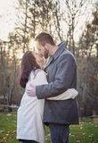 Romantic young couple kissing outside on a cold fall day. A romantic young couple kissing outdoors on a cold fall day with sun setting behind them royalty free stock images