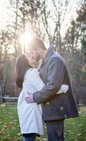 Romantic young couple kissing outside on a cold fall day. A romantic young couple kissing outdoors on a cold fall day with sun setting behind them stock photography