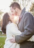 Romantic young couple kissing outside on a cold fall day. A romantic young couple kissing outdoors on a cold fall day with sun setting behind them royalty free stock image