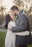 Romantic young couple kissing outside on a cold fall day royalty free stock photography